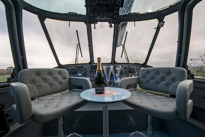 В кабине пилота, где осталась приборная доска, поставили пару крутящихся сидений и столик, сделанный
