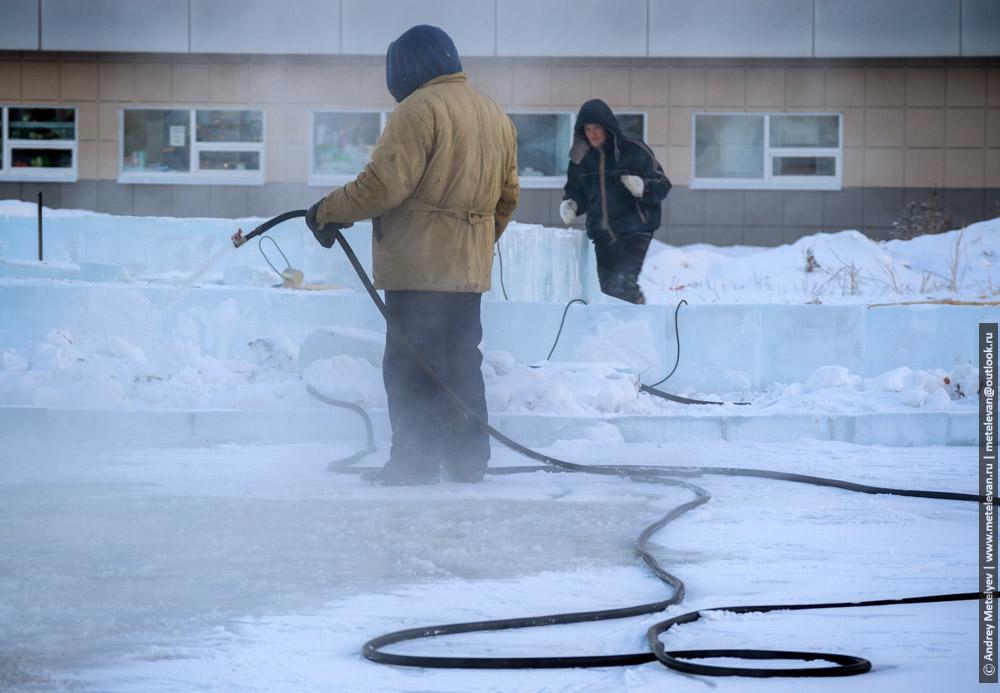 заливают лед работники