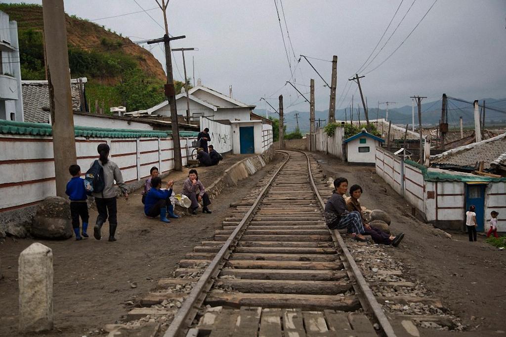9. Люди отдыхают возле железнодорожных путей в одном из городов провинции Hamgyong. (Фото: AP Photo