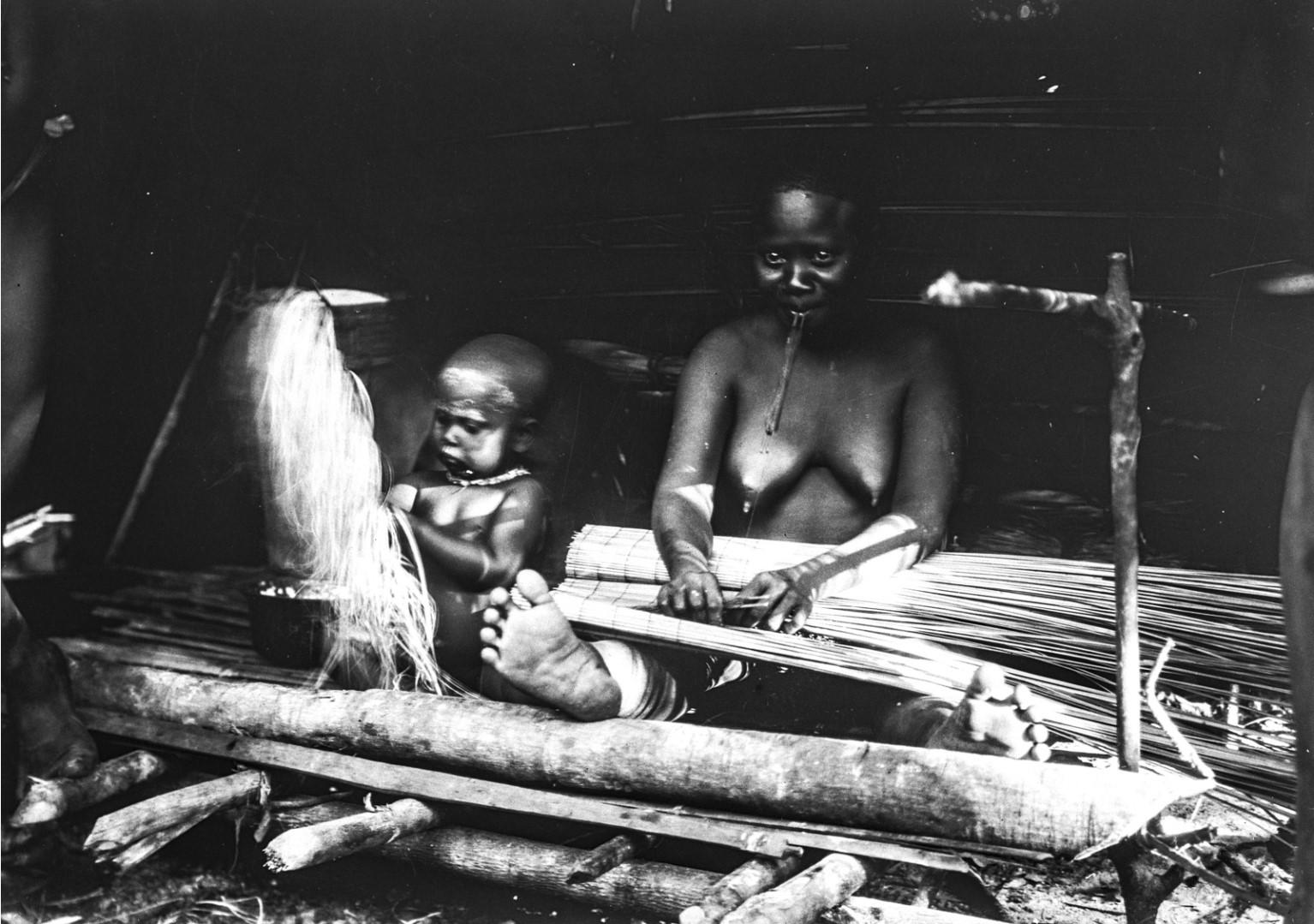1184. Народность онге. Женщина и ребенок плетут циновки