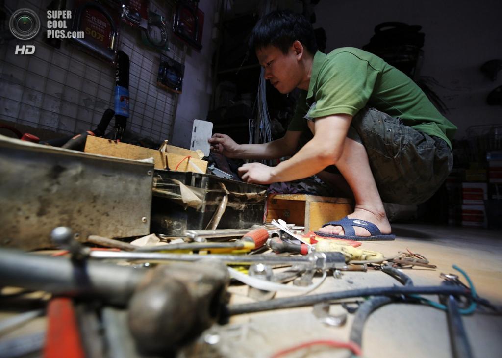 Китай. Пекин. 8 августа. Изобретатель Тао Сянли работает над усовершенствованием своего самодель