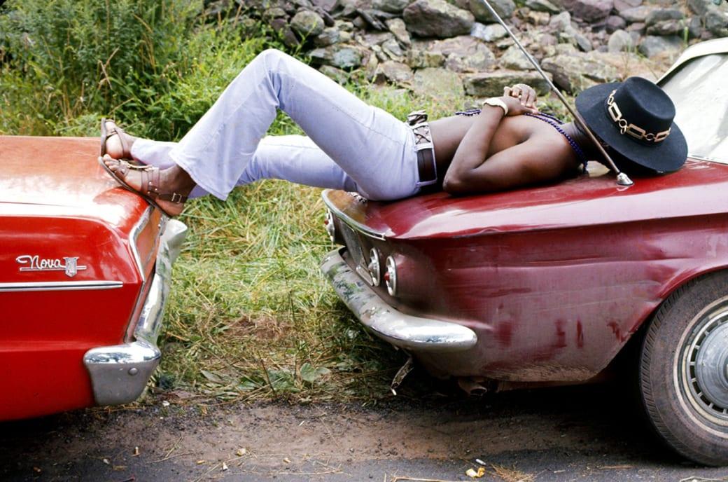Мужчина спит на двух припаркованных автомобилях во время Вудстокской ярмарки музыки и искусств, 1969