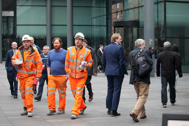 Workers in orange suits with sandwiches go through the Spitalfields market