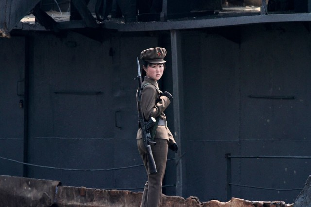 A North Korean soldier stands guard along the bank of Yalu River near the North Korean town of Sinui