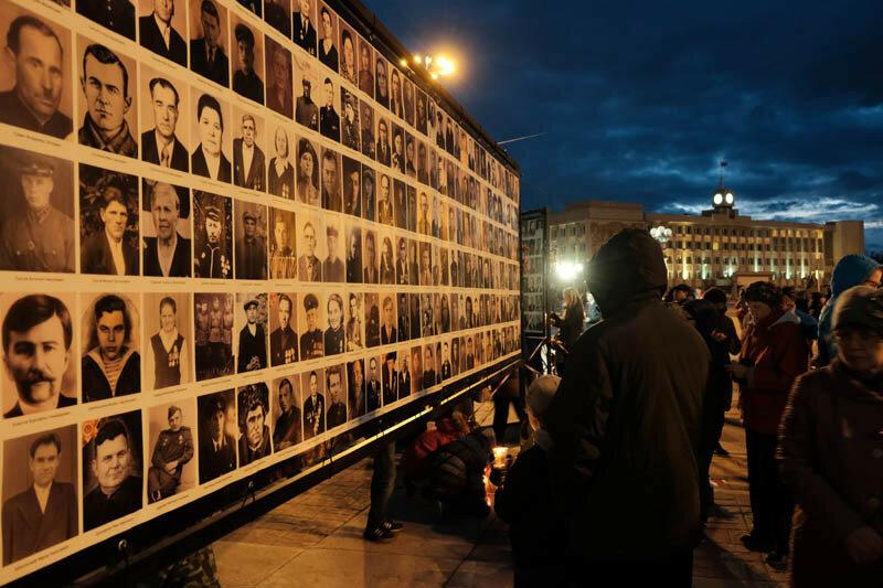 люди стоящие у стендов с портретами воевавших людей