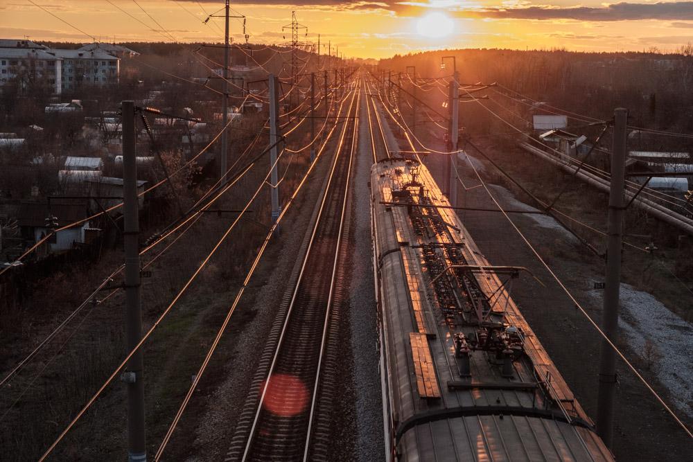 фотография с моста, поезд идет в сторону заходящего солнца