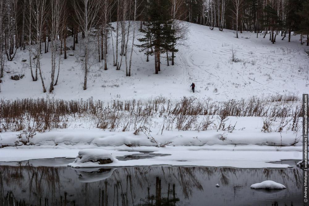 мужчина идет на снежную гору в лесу
