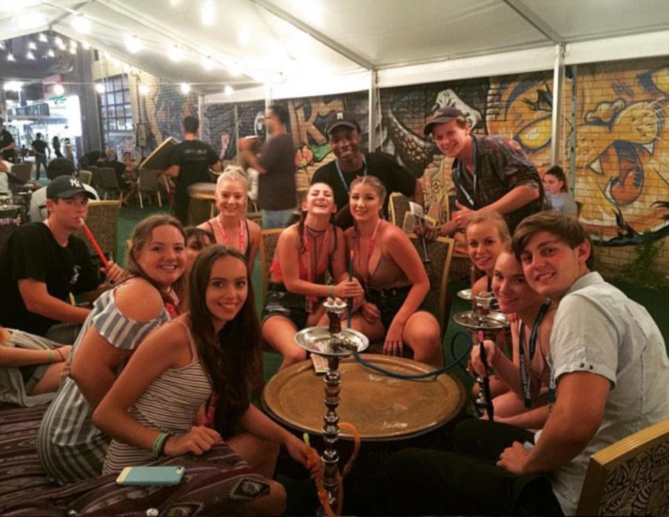 Группа школьников курит кальян в баре.