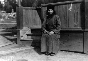Монах-птичник Коневского Рождественского монастыря у крыльца монастырского строения.