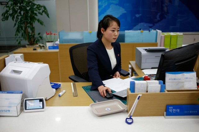 A North Korean employee works in a bank at the Joint Industrial Park in Kaesong industrial zone, a f