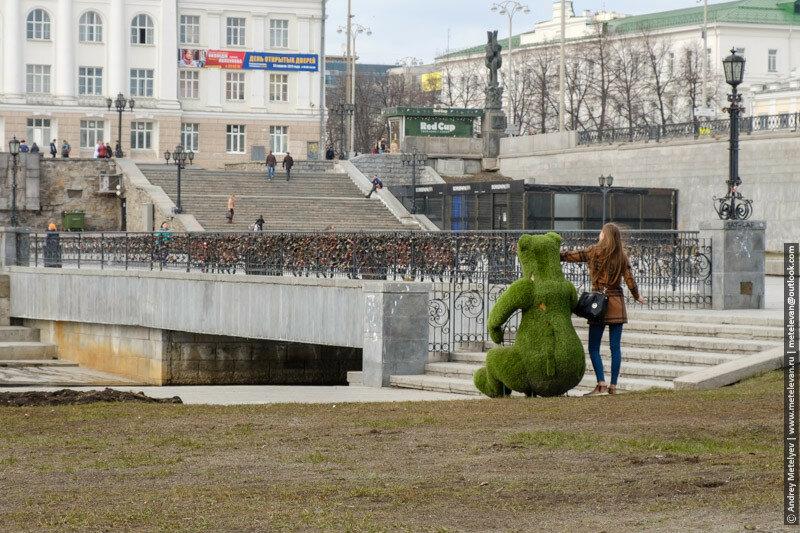 девушка фотографируется с зеленым медведем