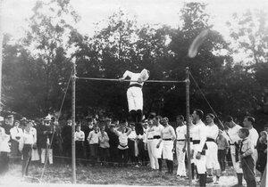 Член Гимнастического общества Пальма выполняет упражнения на турнике