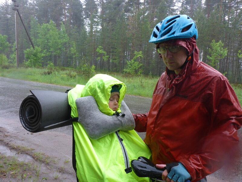 ребенок спит в велокресле с надувной подушкой на шею и в дождевике пик99