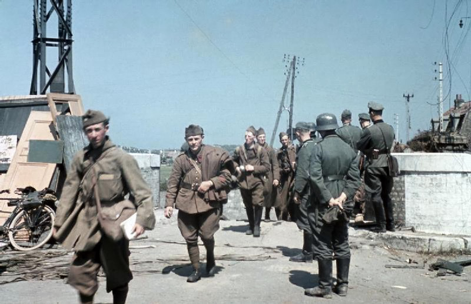 Disarmed French soldiers file pass German officers on the outskirts of Dunkirk.jpg