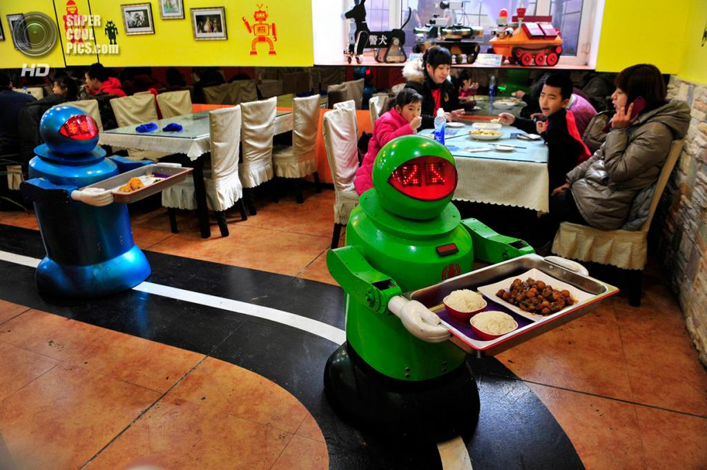 Китай. Харбин, Хэйлунцзян. 12 января. Роботы-официанты разносят еду в ресторане. (REUTERS/Sheng