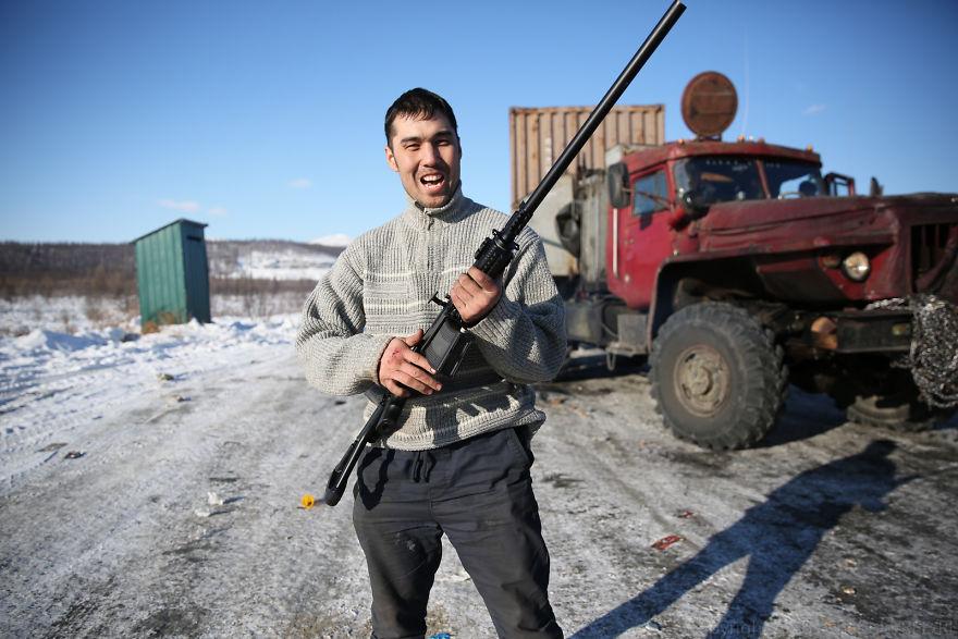 Андрей держит в руках полуавтоматическое ружье на одной из наших стоянок. Руку он повредил, когда ег