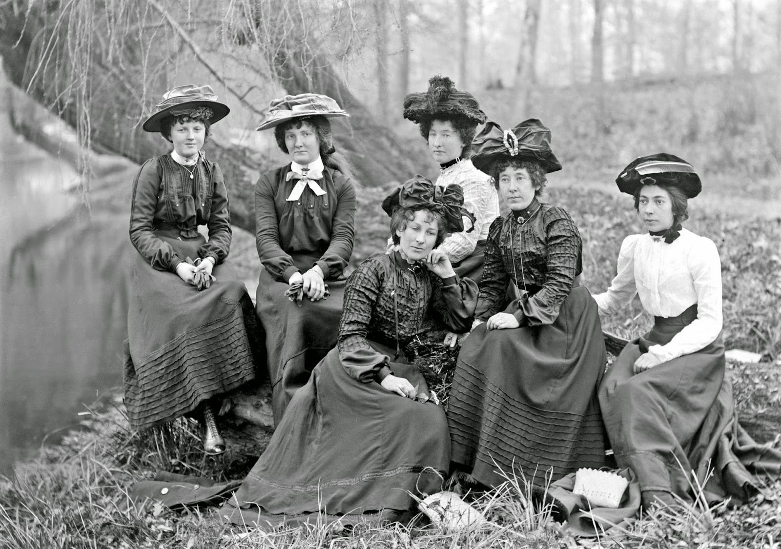 Adam MacLay - Portrait of six women, dressed in finery including elaborate hats, sitting on a river bank, 1905-26.jpg