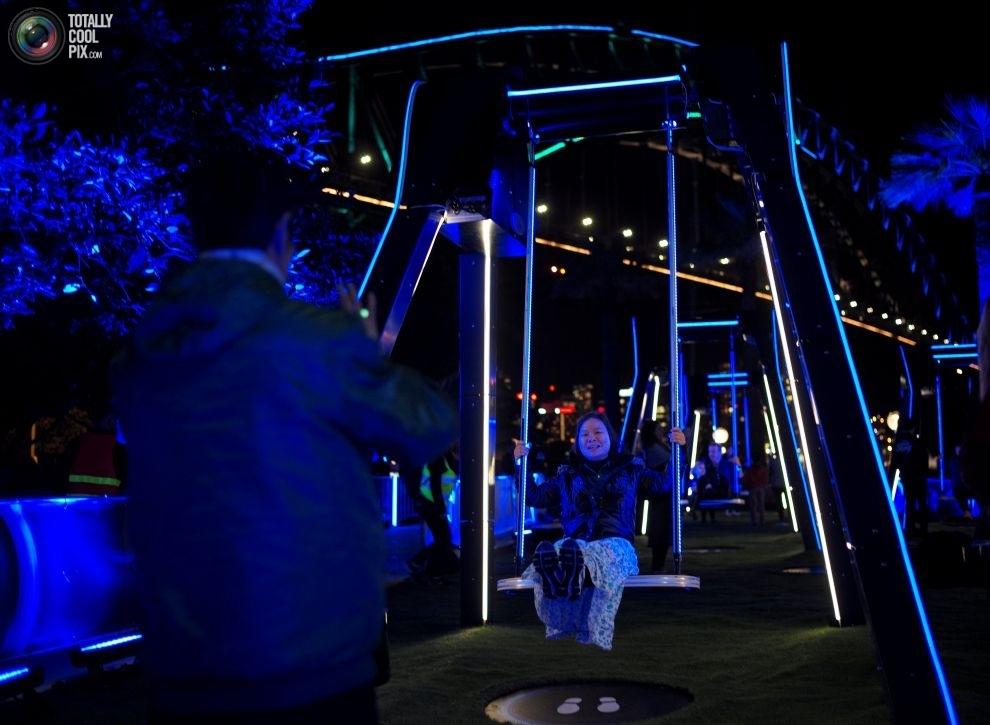 Гости фестиваля музыки и света Vivid Sydney фотографируются на качелях возле моста Харбор-Бридж.