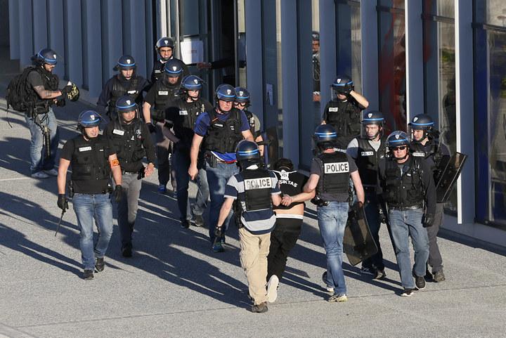 A Besiktas fan is taken away by police before the match