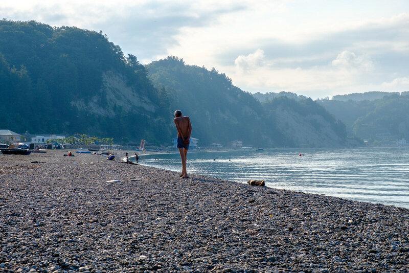 худой человек идет по пляжу, абхазия, рыб завод