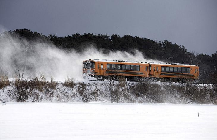 Поезд ходит в зимнее время через тихие сельские пейзажи. (Фото Tomohiro Ohsumi):