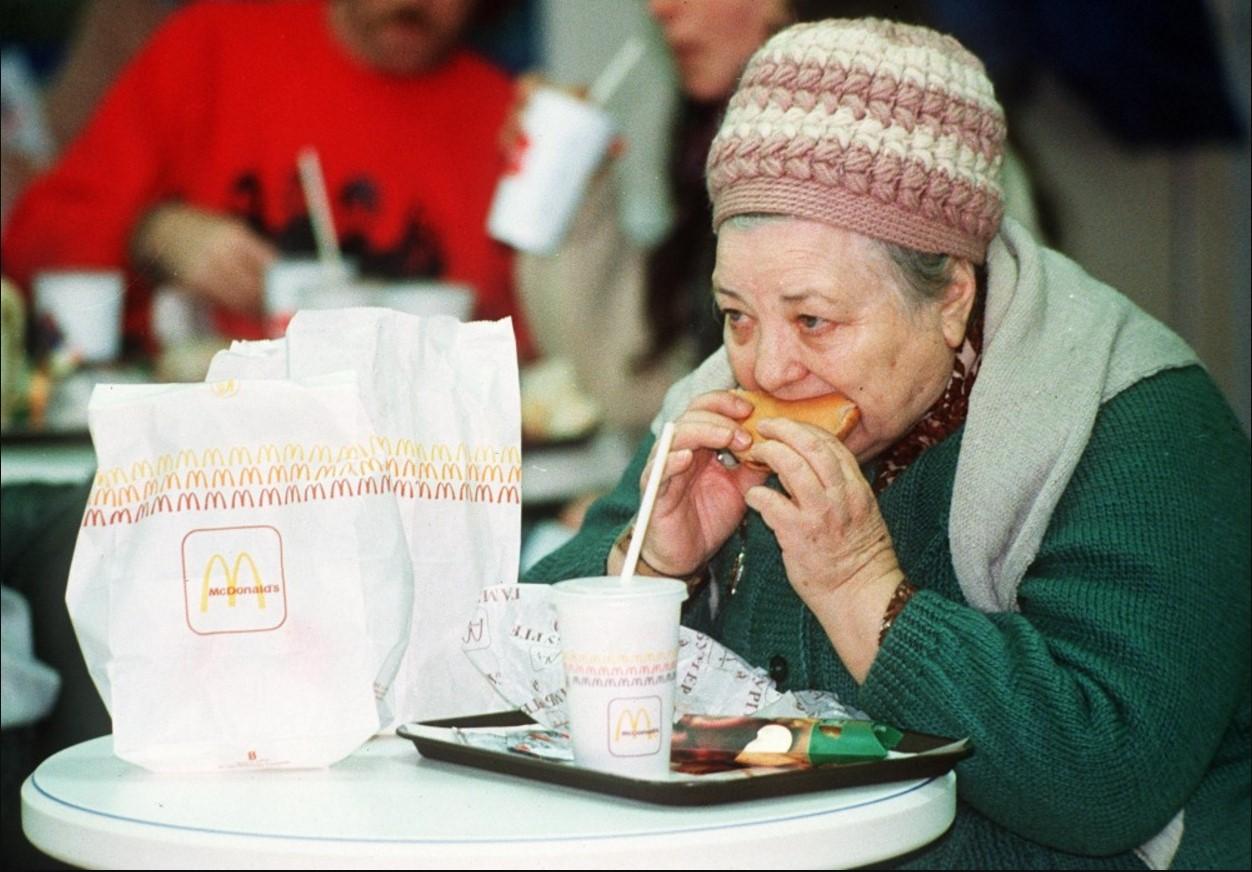 1990. Пожилая женщина ест гамбургер в день открытия первого МакДональдса. 31 января.jpg