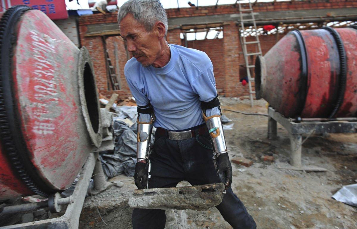 14. Сунь Цзифа переносит камень во время строительства своего нового дома. Китайский крестьянин Сунь