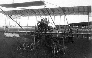 Авиатор с пассажиром на биплане перед подъемом во время праздника.