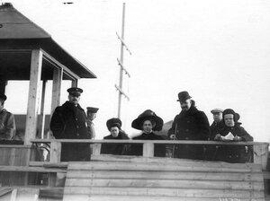 Группа зрителей на трибуне аэродрома во время праздника.