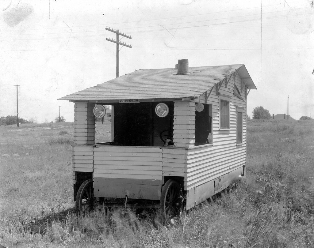 """Move Inn"" camper at Overland Park auto camp in the Overland neighborhood of Denver, Colorado, 1921.  A banner that reads ""Nebraska"" hangs on the side."