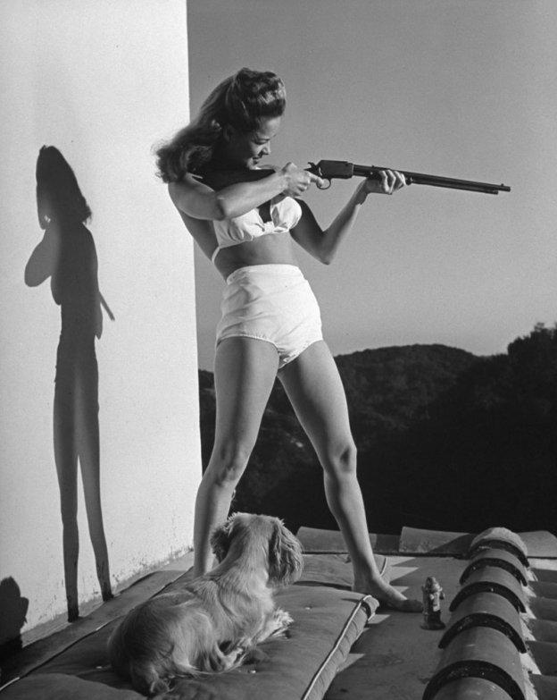 3. Актриса Донна Дрейк с винтовкой на балконе своего дома в Лос-Анджелесе, 1942 г. (Peter Stackpole—