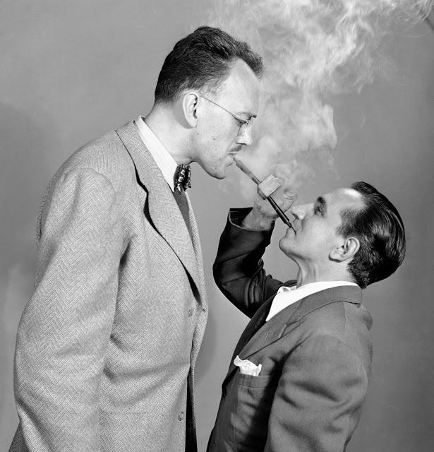 Трубка для двоих Мужчины демонстрируют изобретение под названием «Двусторонняя трубка» (Double Ender