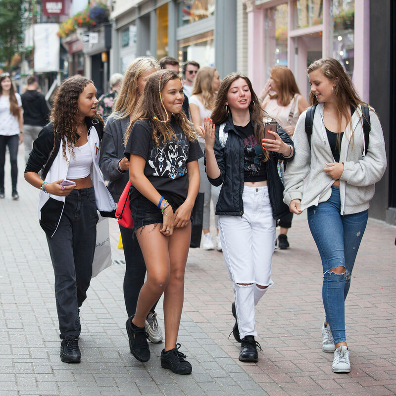 A young teenagers girls walks along Carnaby Street. Carnaby Street is one of the main shopping streets of London.