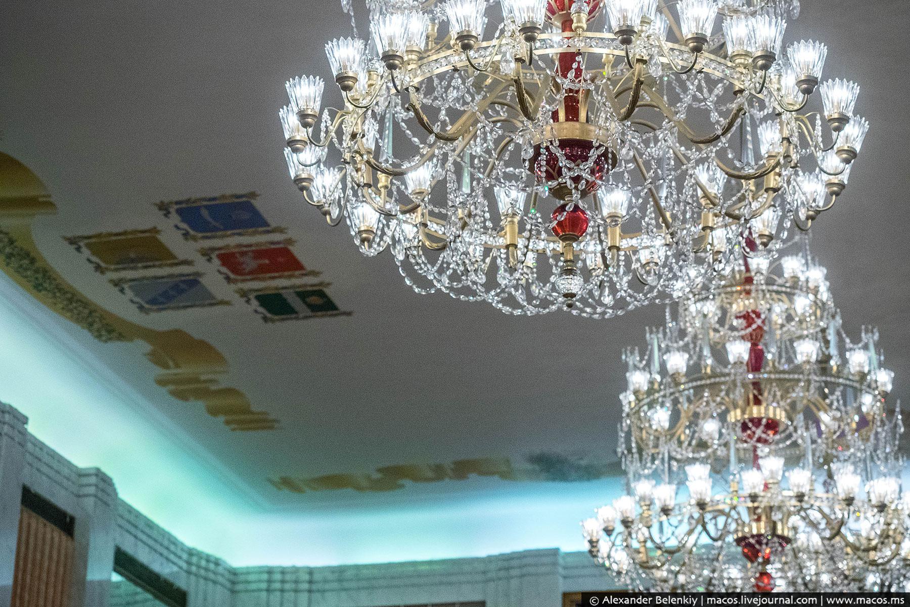 Потолок по периметру украшают гербы российских городов.