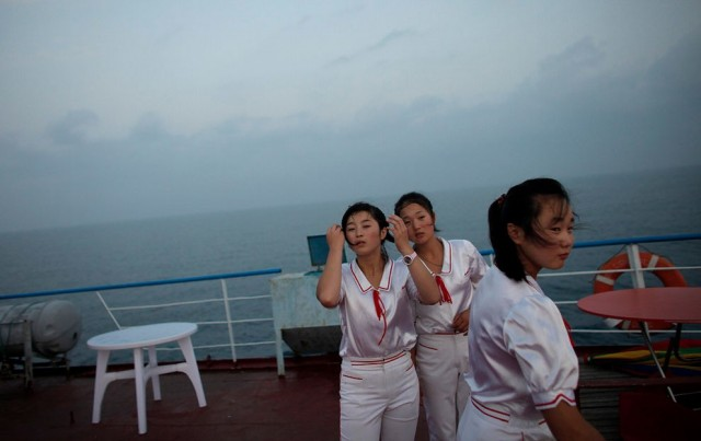 Workers of the Mangyongbyong cruise ship stand on the deck, near Mount Kumgang resort September 1, 2