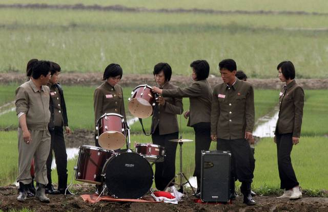 Members of a music group check a drum on a path amid fields as they pack up their instruments after