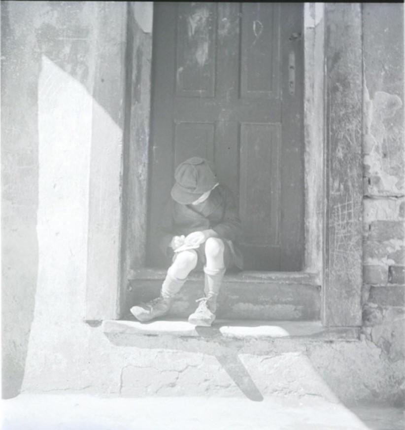 Мальчик пишет записку матери на крыльце дома