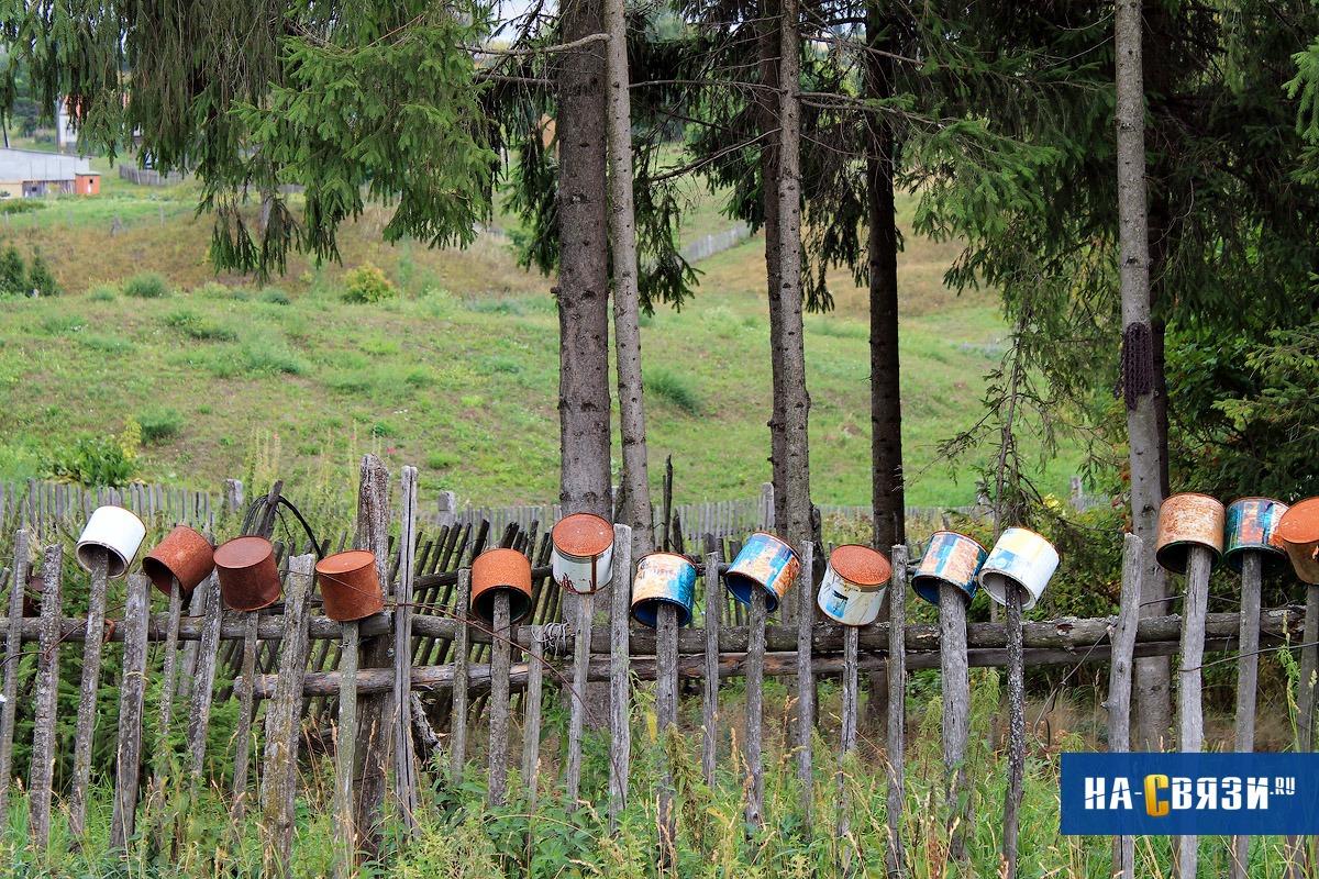 Непринужденно расставленные по кольям ведра придадут забору оригинальный вид.