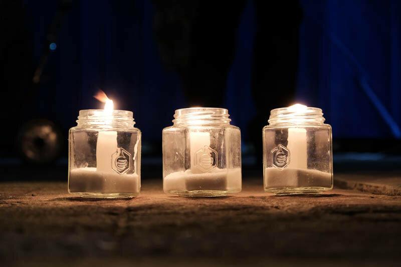 свечи горят в банках возле стендов с портретами - что бы помнили
