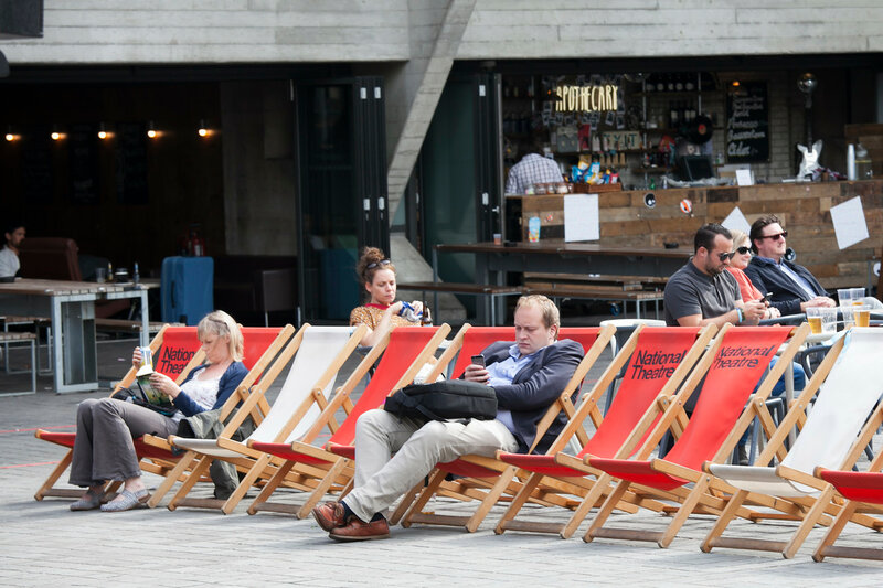 People read books sitting in loungers near the National Theater