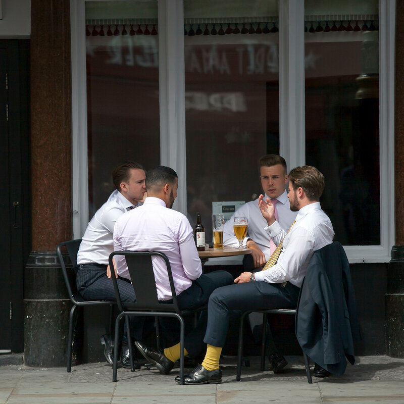 People are sitting in a street cafe near Piccadilly Circus