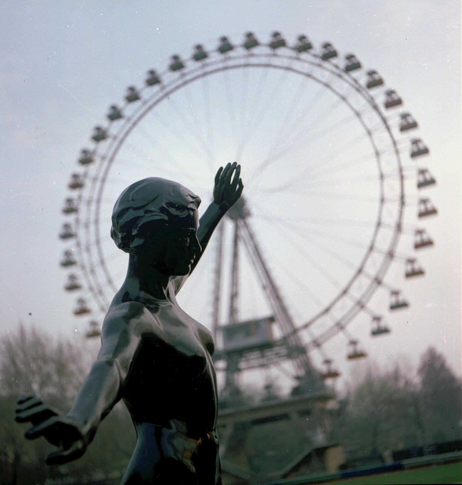 Бронзовая обнаженная женщина возле колеса обозрения в парке Горького