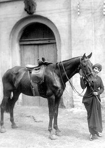 Наездница c лошадью у конюшни.
