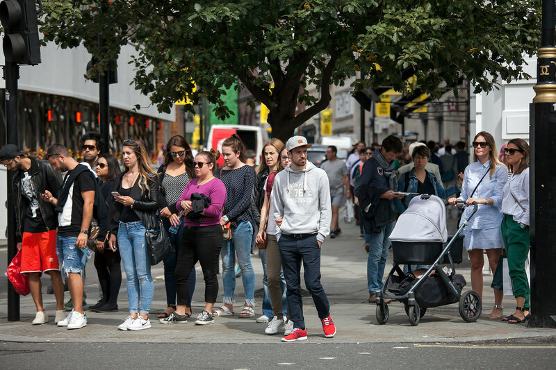 People are waiting for the green light to turn on to cross the road near piccadilly circus