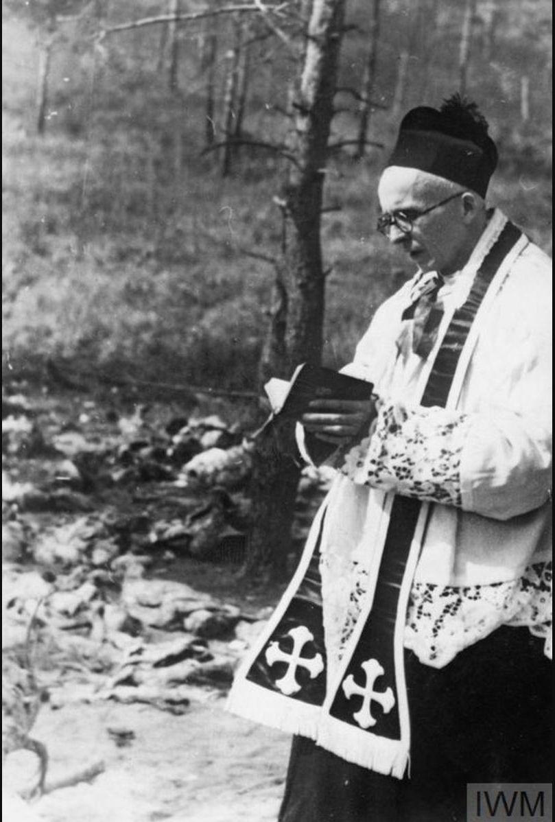 Польский священник, преподобный Станислав Ясинский, молится над  братской могилой