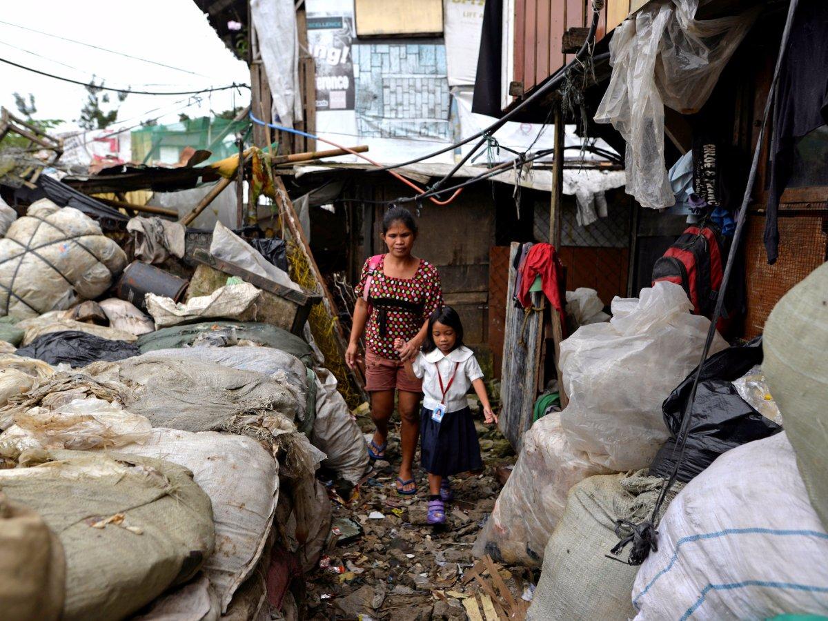 36-летняя женщина идет с дочерью в школу В беднейших районах многочисленные семьи ютятся в самодельн