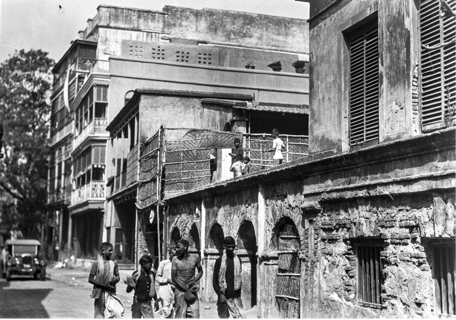 1300. Мужчины на дороге с мешками цветного порошка Холи в Калькутте