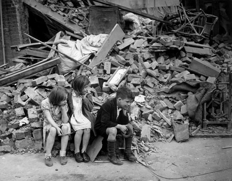 Лондонские дети смотрят на свой дом, разрушенный после немецкого налета на город 15 сентября 1940 года.