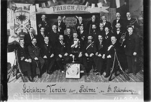 Победители состязаний по стрельбе с наградами на сцене зала Гимнастического общества Пальма во время их чествования