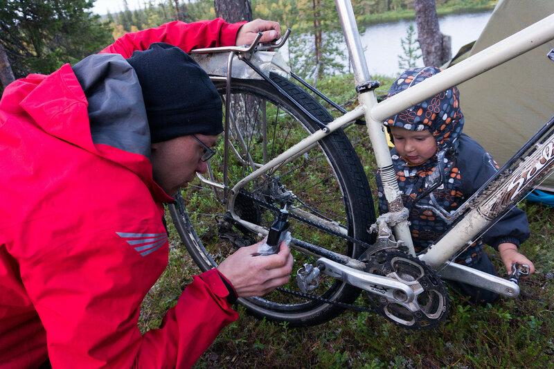 двухлетний ребенок помогает папе смазывать цепь на велосипеде в походе
